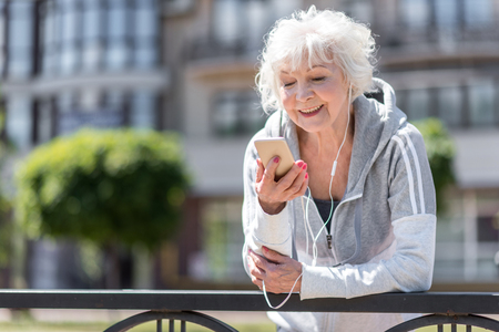 Cheerful old sporty woman listening to music via headphones Stock Photo
