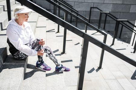 gloom: Cheerless senior woman resting after climbing up stadium ladder outdoor