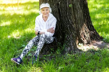 Cheery dame mince senior ayant la relaxation après l'entraînement à l'extérieur Banque d'images - 80179484
