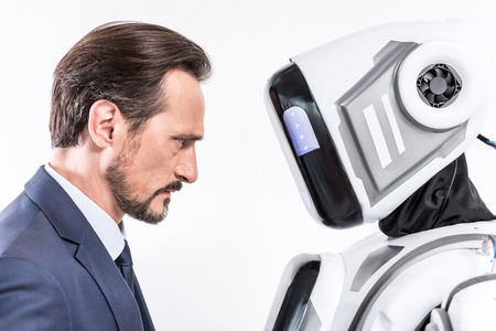 Serious man having eye contact with cyborg