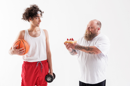 Thick guy seducing thin sportsman by cake Reklamní fotografie