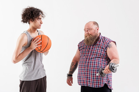 Male thick hipster showing his strength to thin guy Stock Photo