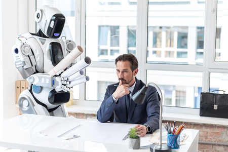 Pensive businessman in suit is working with robot