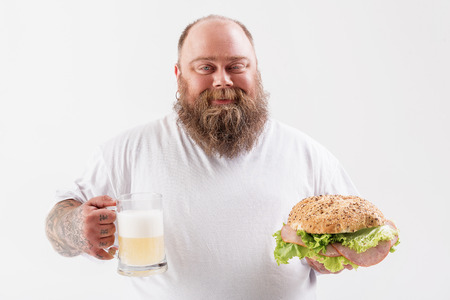 Confident male fatso holding alcohol beverage with burger Imagens