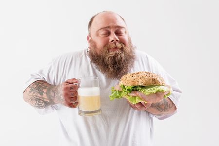 Cheerful thick guy enjoying hold lager with burger