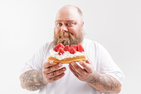 Cheerful thick guy presenting his favorite unhealthy food
