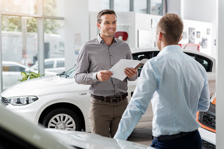 Outgoing client speaking with agent in automobile showroom Stock Photo