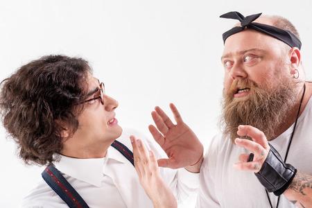 Aggressive fat bearded man molesting slim guy