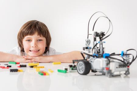 쾌활한 웃는 남자 아이가 로봇을 쳐다 보며 스톡 콘텐츠