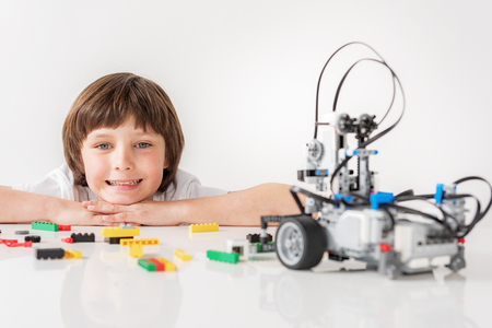 Cheerful smiling male child glancing at robot