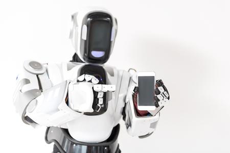 スマート フォンで快適なロボットが立っています。 写真素材
