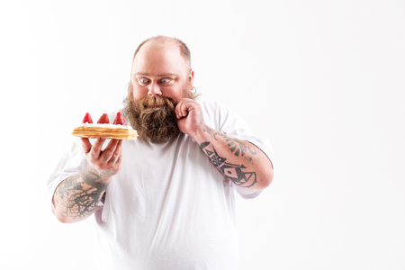 Hungry male fatso looking at cake with desire