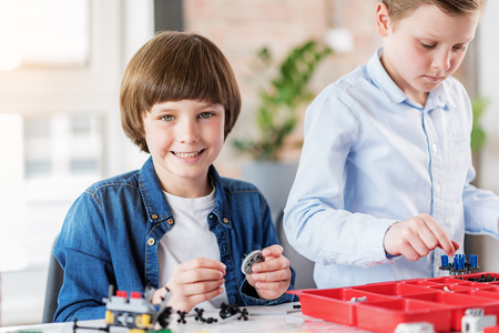 Cheerful smiling male child keeping detail Stock Photo