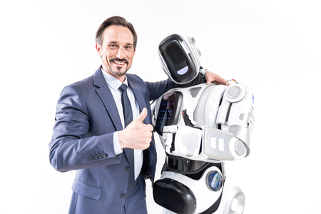 Happy smiling male person embracing cyborg Banque d'images