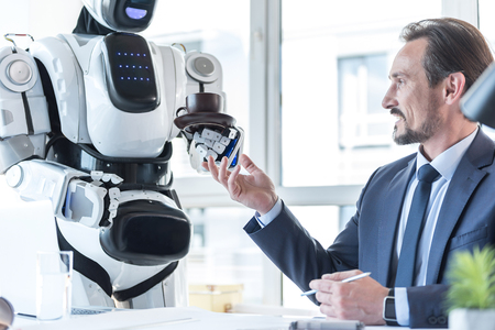 Droid is bringing coffee for pleasant businessman Stock Photo