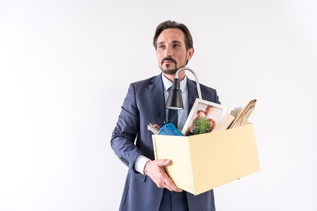 Attractive adult bearded man is holding box with his things