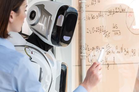 koncentrovaný: Velký cyborg pracuje v kanceláři s elegantní mladou ženou