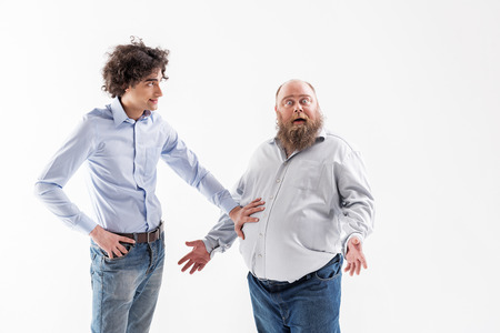 Ironic slender guy admiring of fatty tummy