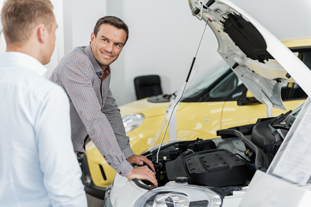 Outgoing male telling with salesman in car dealership