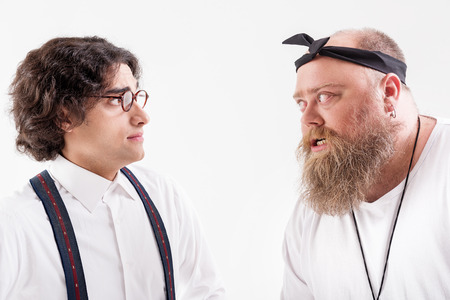Irritated male hipster talking to frightened smart guy