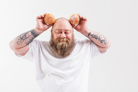 Happy thick guy holding two doughnuts Stock Photo