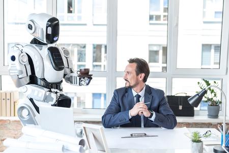 アシスタント ロボットは笑顔の従業員のための飲料をもたらしています。