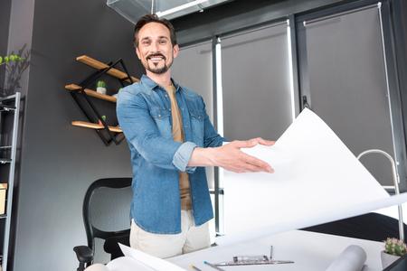 Hilarious smiling man presenting result of work