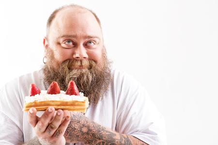 Gelukkige dikke man die smakelijke taart geniet