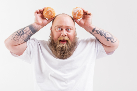 Carefree fat man playing with donuts