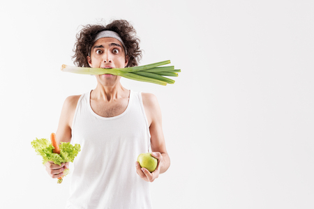 Skinny guy eats only vegetables Stock Photo