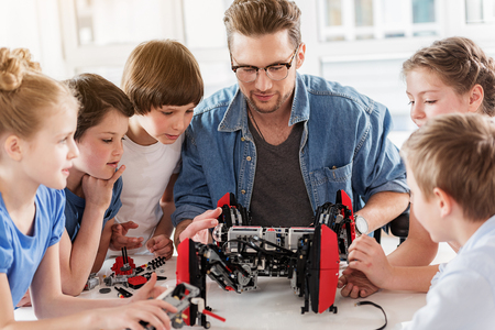 Curious technical team working with robot