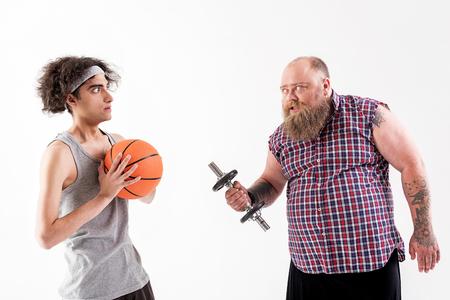 Fat bearded man pestering to slim boy