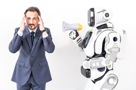 he: Stop yelling. Man wanting to close his ears because of robot holding speaker and he looking at camera with irritation. Portrait. Isolated Stock Photo