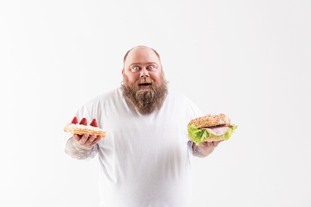 I cannot believe in my happiness. Joyful fat man is holding large burger and cake. He is standing and laughing. Isolated