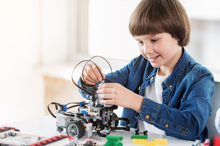 Jolly busy male child is working on robot. He sitting near table in workshop