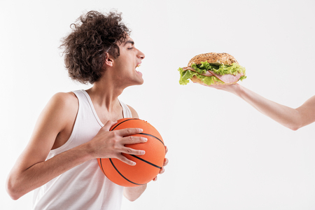 Starving skinny male basketball player is opening his mouth widely while looking at appetite sandwich in female arm. Isolated Stock Photo - 80475227