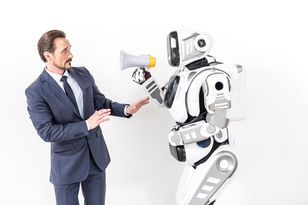 Anxious male person standing near cyborg Stock Photo