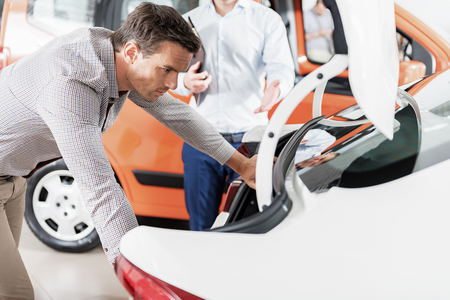 inconvenient: Serene man watching at automobile trunk Stock Photo