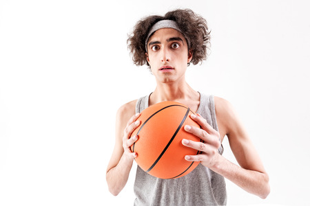Scared slim guy playing basketball Stock Photo - 80596969