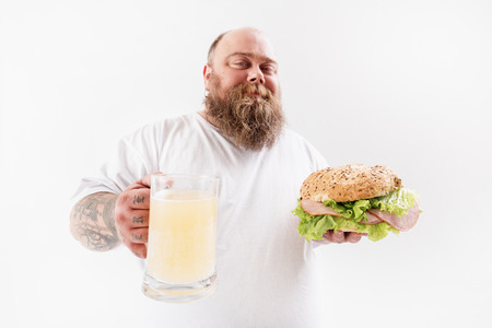 Happy fat man eating sandwich with alcohol beverage