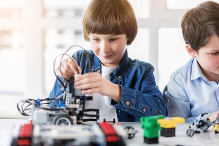 Hilarische kleine constructeur maken speelgoed Stockfoto