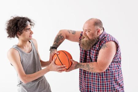 Aggressive thick man bullying young slim guy