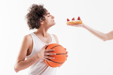 Skinny young man is seduced by sweet unhealthy food Stock Photo