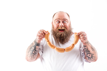 Happy fat man eating meat with enjoyment