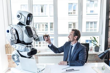 사려 깊은 로봇이 사업가에게 에스프레소를주고있다.