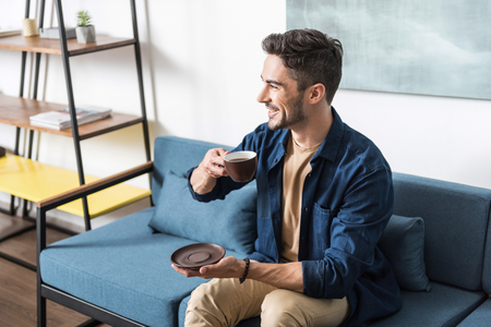 Joyful bearded guy resting on couch with hot drink