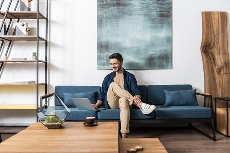 Joyful bearded man working indoors at his living room