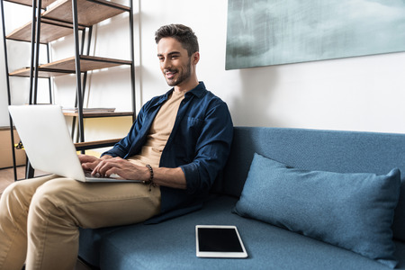 Smiling youthful guy using modern technologies at home Stock Photo