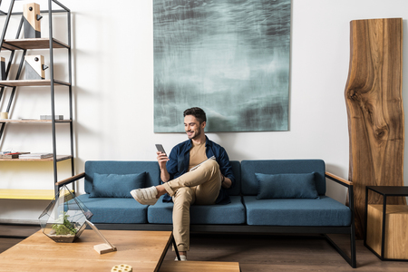 Happy youthful guy bearded resting with cellphone in living room Stockfoto