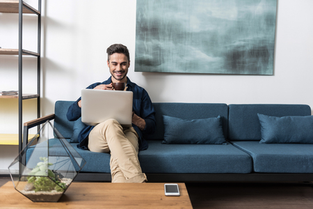 Happy youthful man having rest using notebook at home Stockfoto